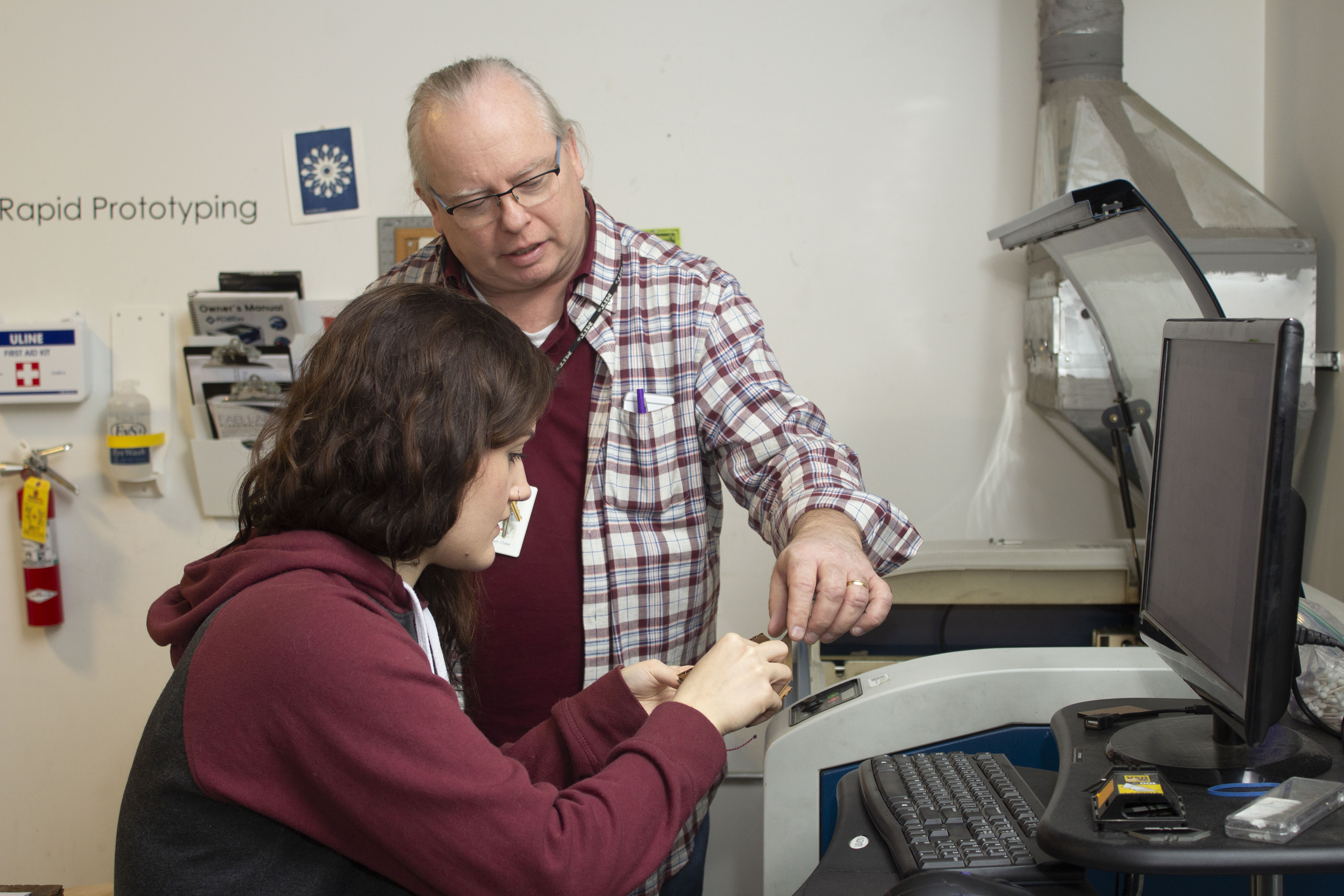 Instructor Joe Chase works with student Sarah Leclair to create a 3D object using a laser cutter.